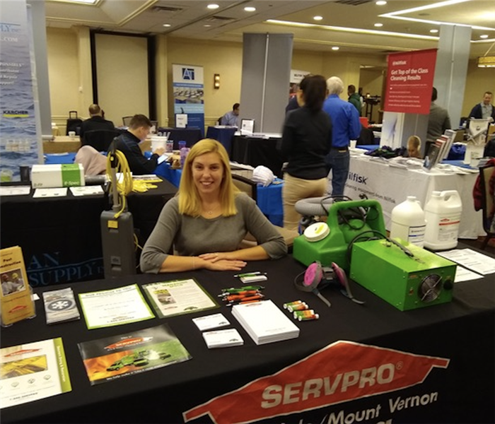 Traci Burrows sitting at SERVPRO table at tradeshow.