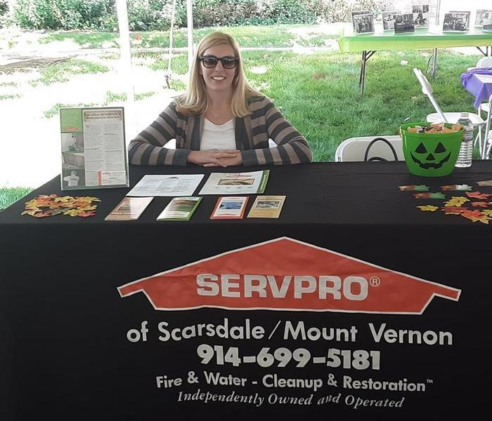a woman sitting at a black SERVPRO branded booth outdoors
