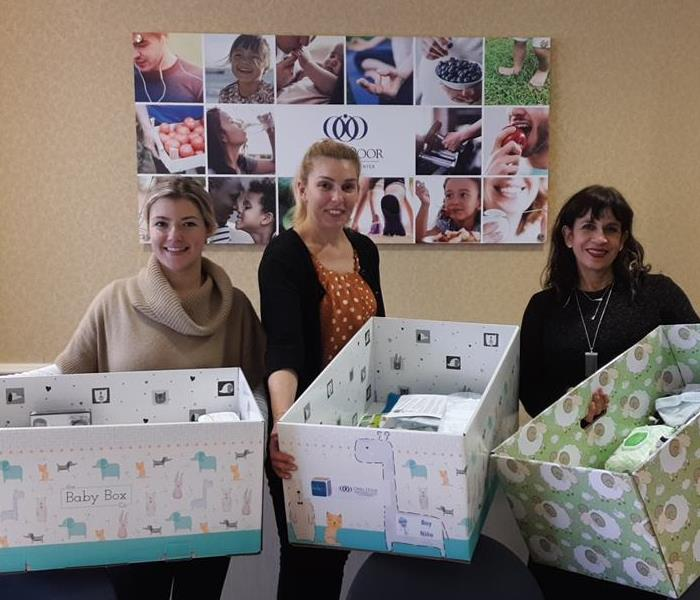 three women holding large boxes full of baby supplies