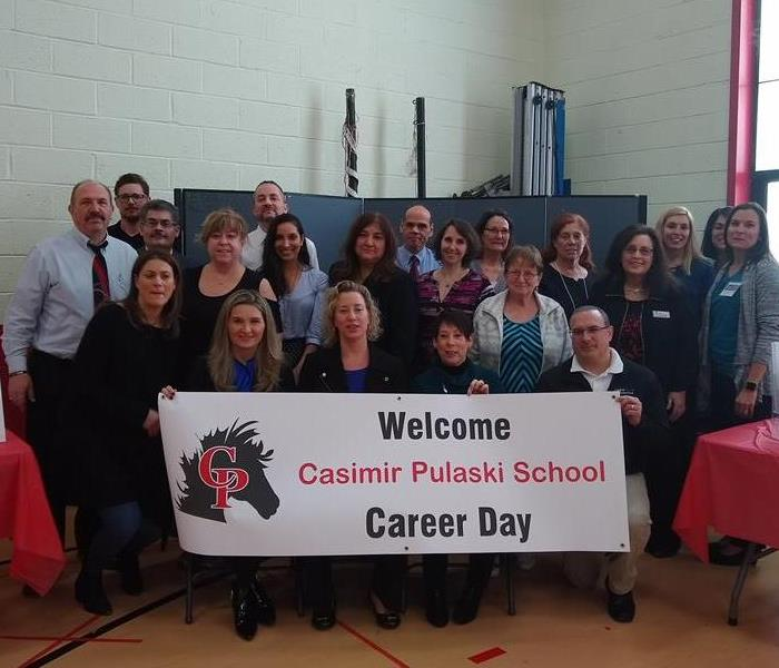 group of people in front of a career day sign