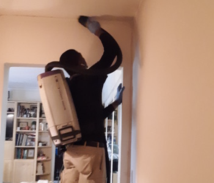 SERVPRO team member standing on a stool cleaning walls and ceiling.