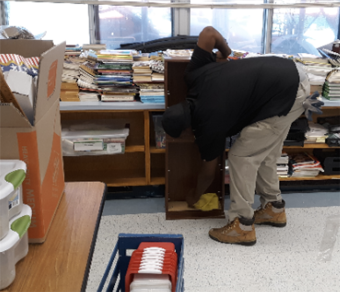 a Servpro worker cleaning a book case in a school