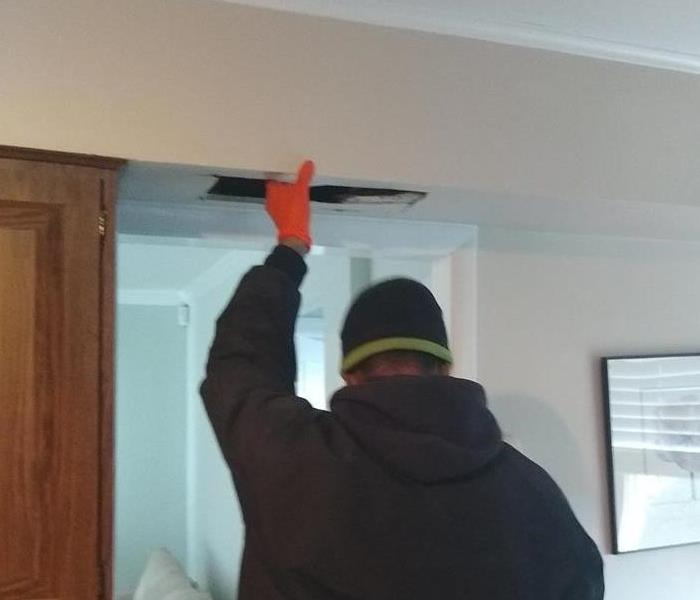 a man inspecting the ceiling of a home
