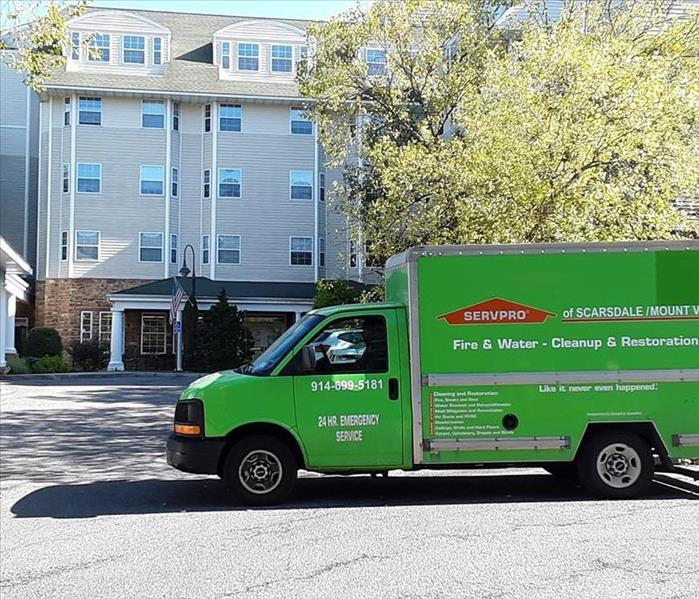 a green SERVPRO truck in front of a commercial building