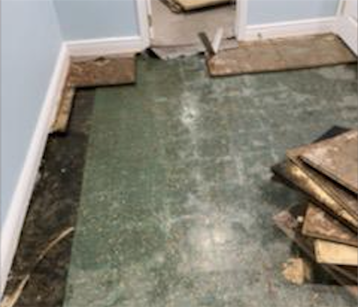 Partially demolished flooring in a small room.