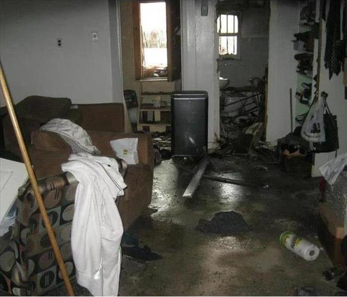 A living room with water and smoke damage on furniture