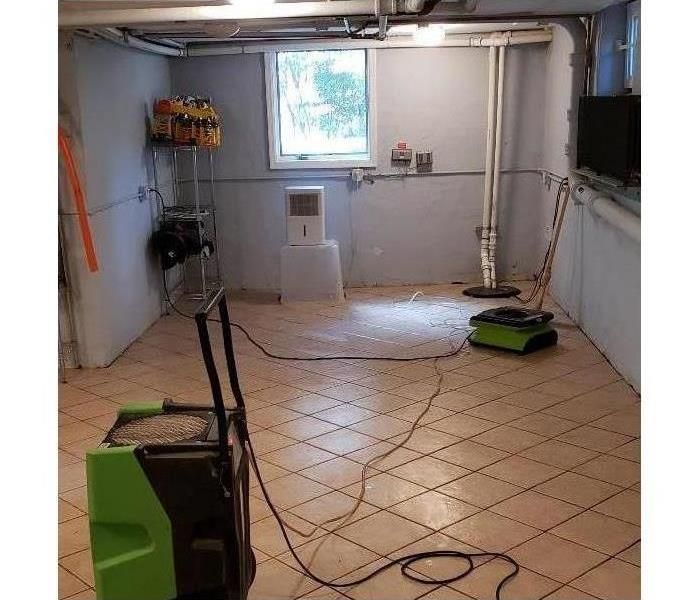 Two air movers placed in a basement drying up area affected after water damage